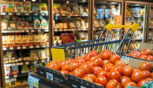 Ein Einkaufswagen für die Einkaufshilfe steht vor einer Kühltheke im Supermarkt.