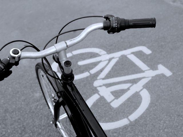 Ein Fahrradlenker über der Markierung eines Radwegs.