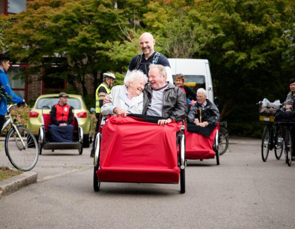 Ein Ausflug mit mehreren Rikschas; im Vordergrund eine Christiania-Rikscha mit einem Fahrer und zwei Passagieren