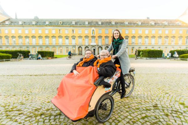 Zwei Seniorinnen auf einer Triobike-Rikscha mit Fahrerin vor dem Gebäude der Universität Bonn