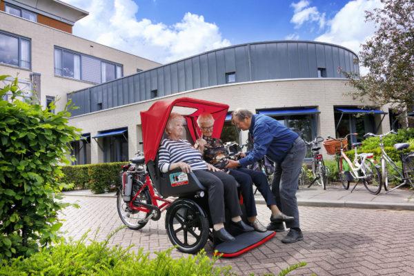 Zwei Seniorinnen in einer Van Raam Rikscha, der Fahrer bereitet die Ausfahrt vor; am Eingang des Seniorenheims